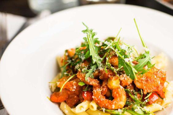 Recept voor pittige pasta voor 4 personen. Met zout, olijfolie, peper, garnaal, verse pasta, pastasaus arrabiata, rucola, courgette, paprika, ui, knoflook en parmezaanse kaas