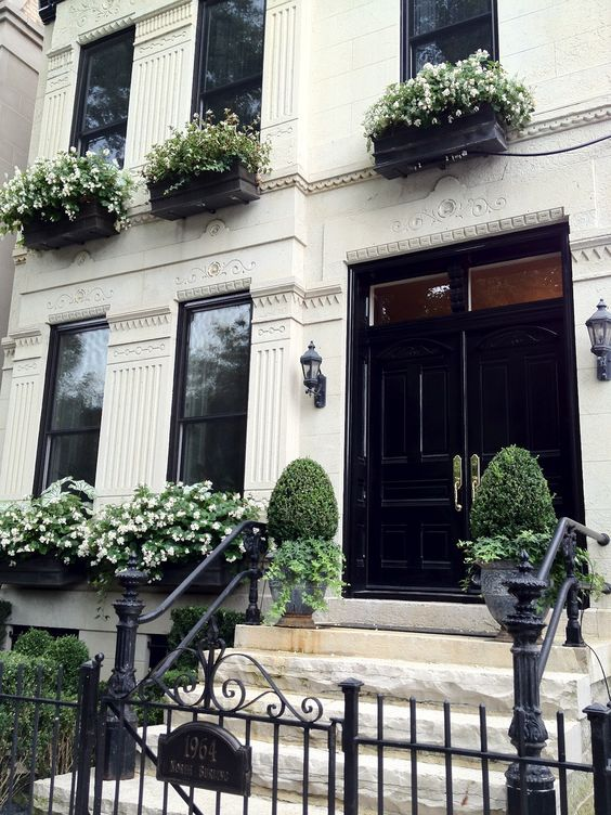 Window boxes a black and white theme, statement doorway, signature railings and big pots either side of the entance