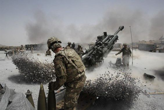 A soldier fires a howitzer out of a gravel pit.