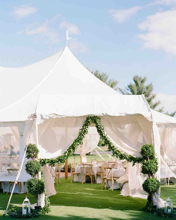 A Summery, Lakeside Wedding in Michigan | Martha Stewart Weddings - After a cocktail hour on the lawn by the lake, where guests relaxed while a jazz band played, everyone moved towards the reception, entering the tent, which was framed by garlands of greenery and a pair of tiered topiaries.