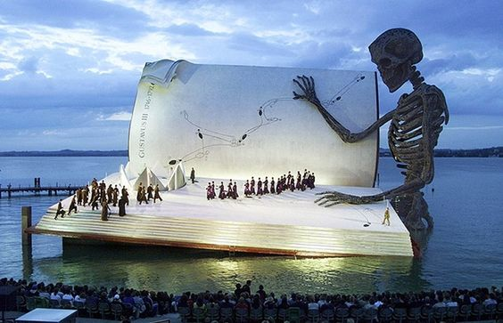 """Seebühne (or floating stage), with 7,000 seats, is the location for large-scale opera or musical performances on a stage over water on the shores of Lake Constance in Bregenz, Austria. Bregenzer Festspiele (Bregenz Festival) is a performing arts festival which is held every July and August in Bregenz, Austria. The festival has become renowned for its unconventional staging of shows. Verdi' s opera """"A Masked Ball"""" performed at Seebühne in 1999 featured a giant book being read by a skeleton."""