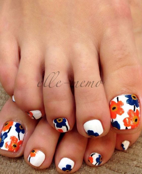 A cute and colorful flower inspired toenail art design. Using white as the base coat, blue and orange flowers grace the toenails giving a bright and colorful painting of blooming flowers on your nails. Perfect for the summer weather.