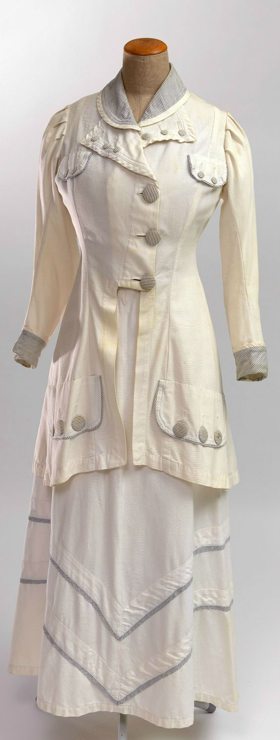 Two-piece tennis dress for ladies, c. 1908. Hip-length jacket and skirt of white cotton grosgrain; buttons, collar, sleeve cuffs and piping of grey and white striped cotton. Collection of Wien Museum, via Google Cultural Institute.