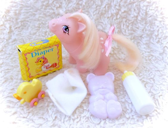 A very stunning 1984 G1 My Little Pony Baby Cotton Candy that is nearly complete with many MATCHING original accessories - baby diaper, baby bottle, baby diaper box, comb, duck toy, and a hair ribbon. Cotton Candy herself is in very good condition with minimal/minor flaws nly. Please see all pictures up close for a thorough representation of the item! I have TONS more cute vintage items for sale in my Etsy shop - check it out for SUPER CHEAP combined shipping discounts. ;) I ship WORLDWIDE…