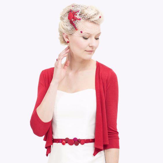 Modisch, mutig, rot! Mit neuen Knopfapplikationen und einem knielangen Look kommt Brautkleid Martha daher. In diesem Modell vereint sich ein herzförmiger Ausschnitt mit einem sanft schwingenden Rock, an dem eine versteckte Zierkante aus Tüll den breiten Ziersaum aus roter Dupionseide betont. Für einen weiteren leuchtend roten Akzent kann die Braut einen passenden Kurz-Bolero aus Seide oder eine Stola zum Outfit ergänzen. Im Headpiece und als Halskette setzen die seidenbezogenen Knöpfe…