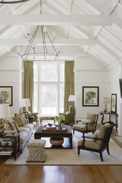 Green curtains, green patterned accent chairs, green accent pillows on cream couch.