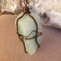 """Raw Aquamarine Wire wrapped Pendant. Antiqued Brass wire. Very large and pretty stone. Measures 1.75"""" long, 1.5"""" wide and 1.5"""" deep. Perfect for a long pendant necklace.  Aquamarine is the Stone of Soothing. It encourages compassion and tolerance, suppresses anger and hostility, and releases an..."""