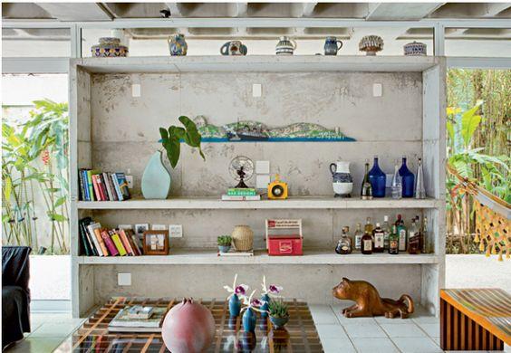 Solta do teto, a estante é uma caixa de concreto. Fechada no alto por caixilho com vidro fixo, tem prateleiras do mesmo material. O projeto é do arquiteto Gustavo Calazans