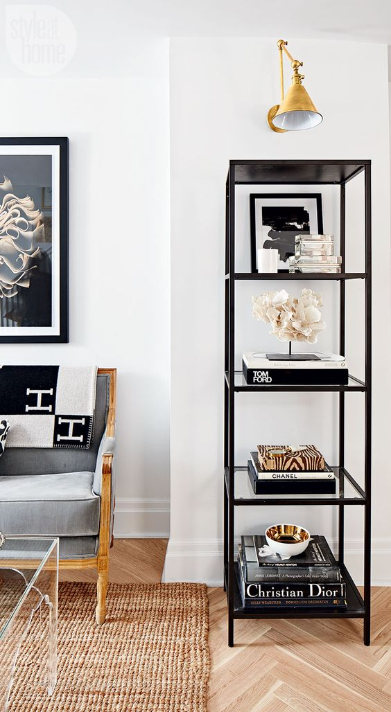 An elegant étagère neatly shows off a collection of inspiring coffee table books and objects