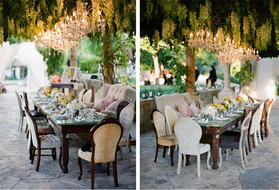 outdoor reception beneath chandeliers with mismatched vintage chairs.