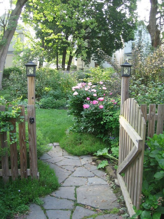 Flagstone pathway through a wooden gate...going into a backyard flower garden area(gate and lanterns)