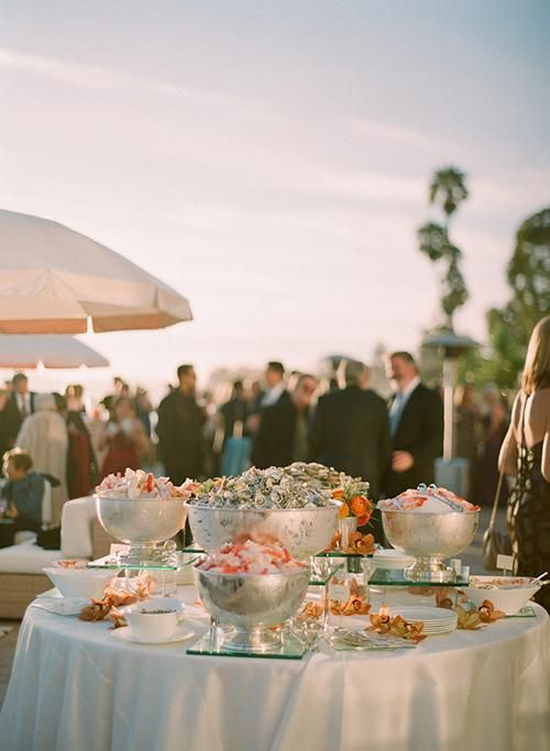 A glorious raw bar displayed on ice in elegant footed bowls | Brides.com