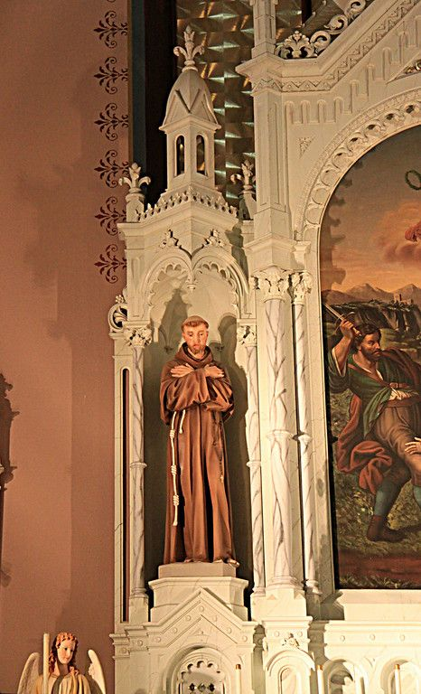 To the left of the painting, arms folded in prayer, is a statue of St. Francis of Assisi, founder of the Franciscan Order. St. Fidelis church and cemetery, Victoria, KS