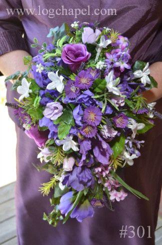 A purple silk cascading bridal bouquet.  www.logchapel.com