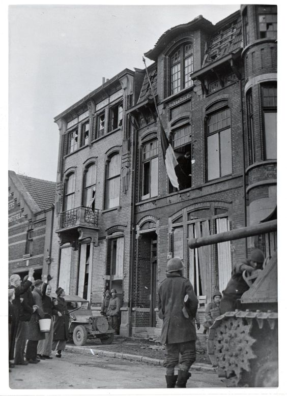 American soldiers stand by with a tank and jeep as Dutch civilians raise the flag of the Netherlands in liberated Venlo after nearly five years of Nazi occupation.  March 2, 1945