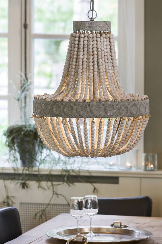 Stunning Wooden Bead Chandelier.In two sizes.This showstopping chandelier is made by hand from hundreds of wooden beads and looks beautiful lit or unlit. Perfect above a dining table, in an entrance hall or kitchen, or a decadent bedroom. It comes with the steel ceiling rose as shown and 3ft of flex and chain link that can be shortened to any length. Takes an E27 (large screw) bulb and is dimmable.Metal frame and wooden beads.Small: approx. 36cm dia x 46cm high Large: approx. 49cm dia x 59cm...