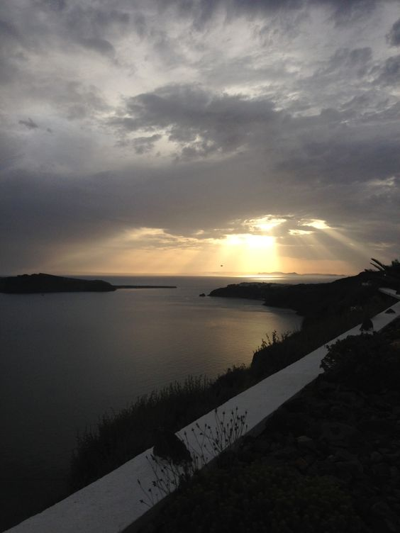 Sun about to set in a cloudy Santorini, view from Imerovigli