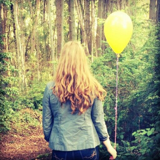 Girl walking in forest with yellow balloon
