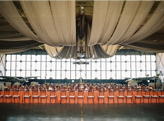Reception in an airplane hangar?! YES, PLEASE! Airplane Hanger Wedding Reception Venue Tables Centerpieces Flowers Decor Coral Beige