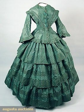 """American Green Silk 1850s day dress: 2-piece taffeta woven en disposition, fitted bodice w/ peplum & large pagoda sleeve, skirt w/ 3 tiers, knotted & fringed frogs, attached paper tag """"Aunt Sallie Hendrickson's green silk dress Woluford Original"""", Sh-Sh 17"""", B 37"""", W 24"""", Skirt L 42"""",(small bodice stain, 1 frog repaired & underarms repaired) excellent."""