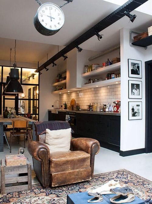 Beautiful industrial style open plan kitchen. beams of light and low hanging lights! Vintage rug and chair