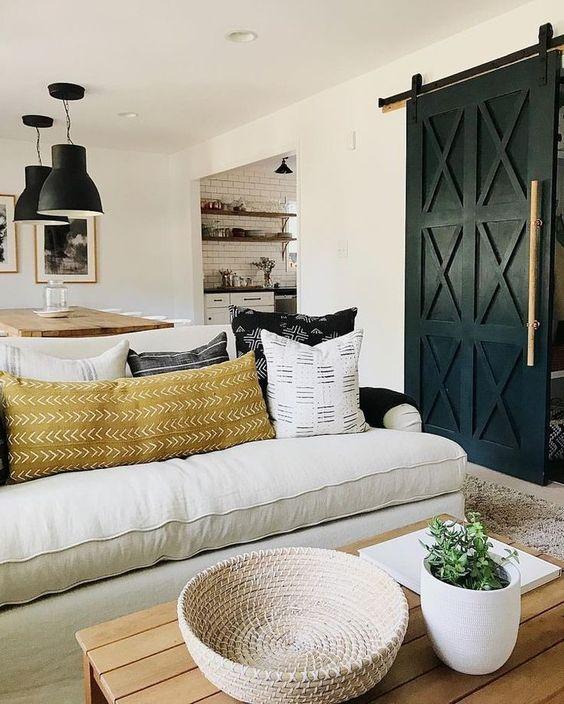 Black and white living room with bohemian decor and modern farmhouse style, black painted barn door, and black Ikea pendant lights. #blackandwhite #decorinspiration #livingroomdecor #bohemian #barndoor