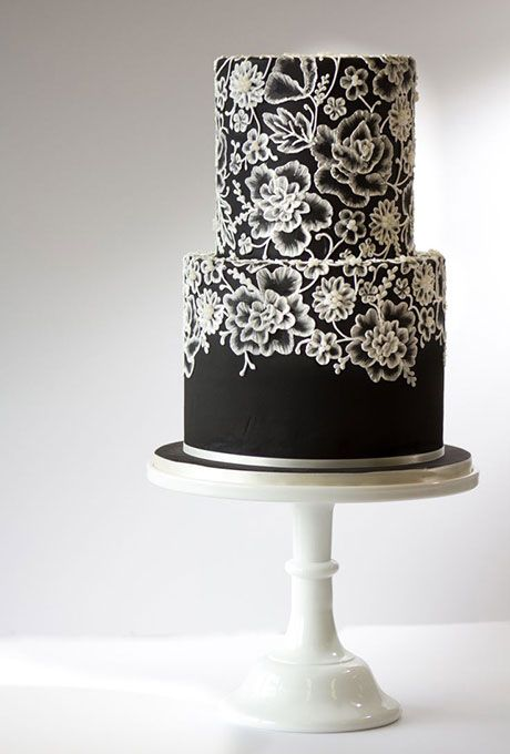 """Brides: Two-Tier Black Wedding Cake with White Lace Pattern. This bold confection by Amy Beck Cake Design proves that a black cake can be beautiful. The lace pattern was created using """"brush embroidery""""— a technique where a paintbrush is stroked through royal icing to mimic stitched embroidery."""