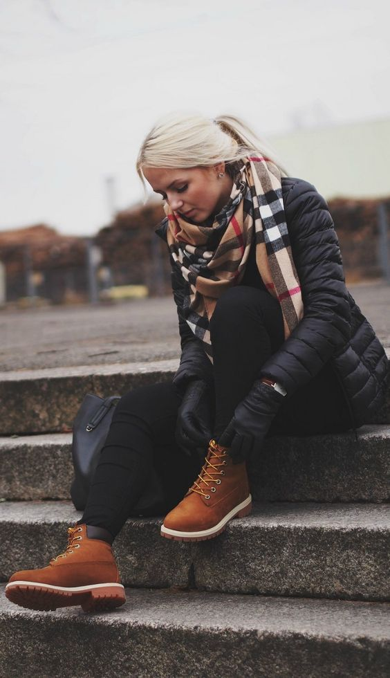 Don't be afraid to branch out from the classic tan coloured Timberlands! Elizaveta Pechuyeva shows just how stylish a darker style can be, wearing these boots with a gorgeous oversized scarf and a puffer jacket. Jacket: Lindex, Jeans: BikBok, Bag: Mango, Watch: Daniel Wellington. #Timberland #Fashion: