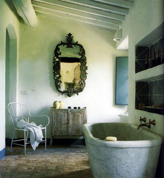 Baño rústico con bañera de mármol, espejo reutilizado, suelo de ...