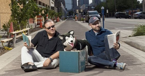 Travis DiNicola (left) and Alex Mattingly of Indy Reads Books, along with a faux dog provided by City Dogs, hang out on the Cultural Trail in front of their soon-to-open store. Photo by Stephen Simonetto