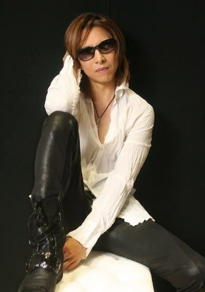 白いシャツに黒いパンツをはいて膝を立てているXJAPAN・YOSHIKIの画像