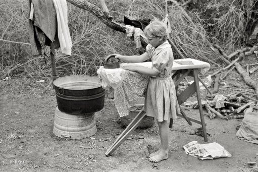 1939  Child of white migrant worker ironing in a tent camp near Harlingen TX