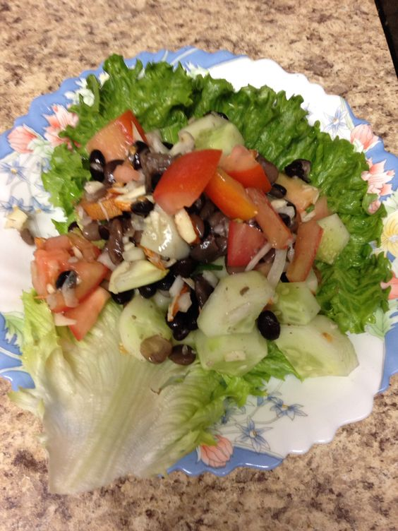 Beans and cucumber salad with lemon dressing.                      ( Includes half chopped onion, 1 tomato, 7-8 raisins, 5-6 roasted sliced almonds, one small cucumber and a leaf of romaine lettuce)