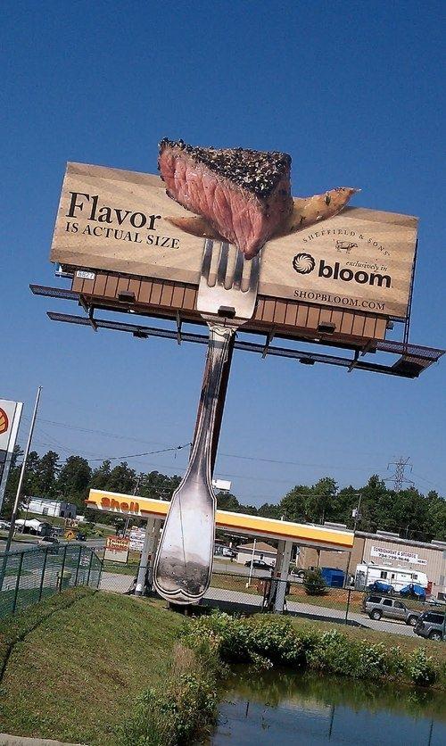 """""""L'épicerie Bloom a érigé au bord de la route un affichage géant. Le billboard represente un gargantuesque morceau de viande au bout d'une fourchette, accompagné d'une frite et surmonté du slogan « flavor is actual size » (saveur grandeur nature) Bloom Grocery a mis en place un système de diffusion d'odeur qui couvre toute la zone et nottament la station service voisine. Le panneau diffuse une odeur chimique de barbecue."""" http://lareclame.fr/bloom+grocery+marketing+olfactif"""