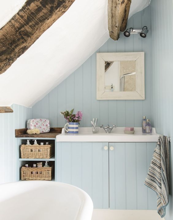 Exposed beams, rattan baskets and a blue colour palette give this country bathroom a subtle coastal vibe