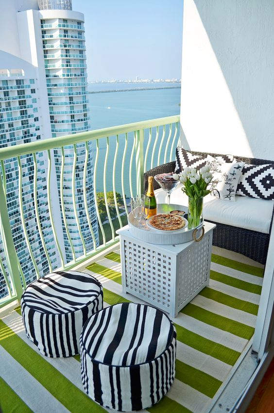 Outdoor Decor: Outdoor living can be a stylish extension of your living area. This small balcony was converted into a cozy space by adding a bold, striped rug from HomeGoods and comfy seating for lounging and entertaining. Tip: Pick a bright accent color and keep everything around it neutral such as black and white. This will create a refreshing modern space! (Sponsored Pin):