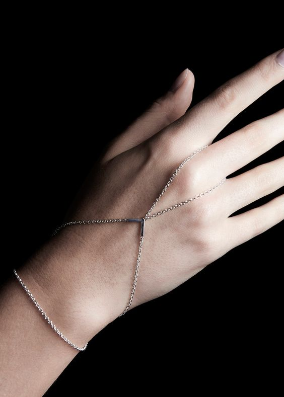 Fine cable chain loops around the middle finger and cris-crosses the back of the hand by way of a solid right angle shape. All #chain lines meet inside the #wrist at a spring #ring.