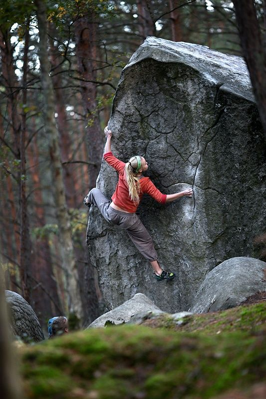 Woman spread out as she is hanging on to a large rock