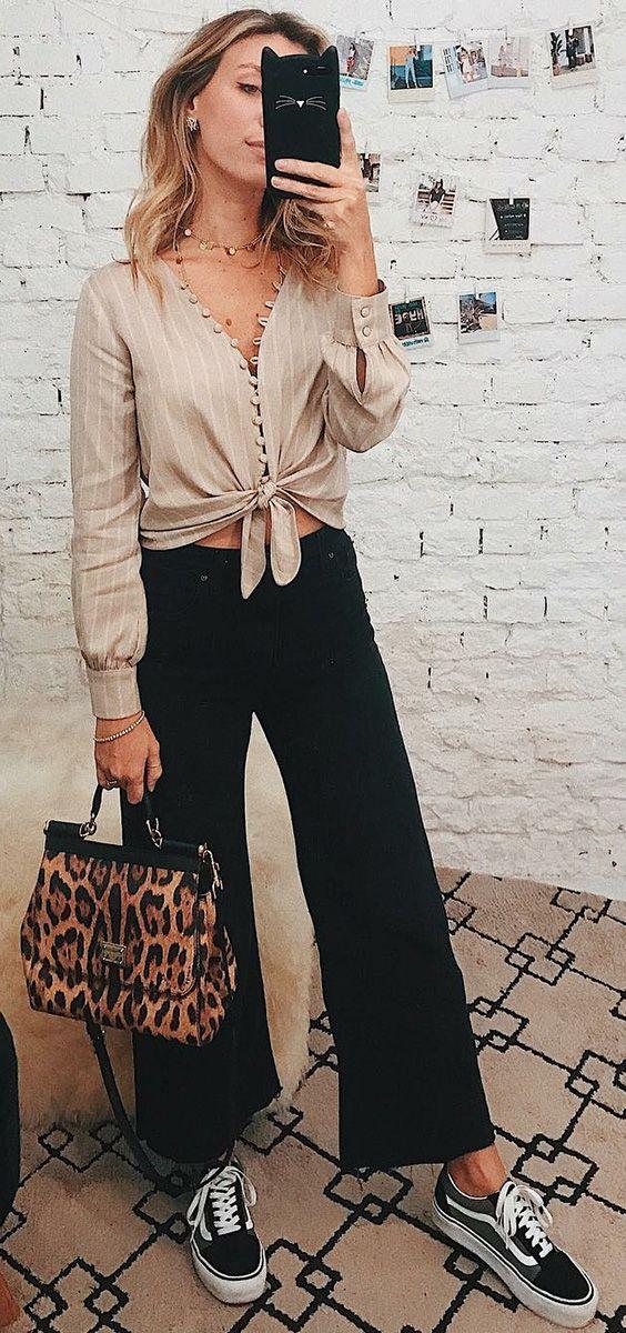 10 looks para quem ama praticidade. Camisa bege listrada com botões e nozinho na cintura, calça preta larguinha, whide leg jeans, tênis preto vans