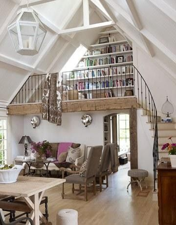 so much appeal ! white board & batten ceiling , natural wood trimwork  & black Iron stair rail . arched doorways . built in shelving & that loft !!