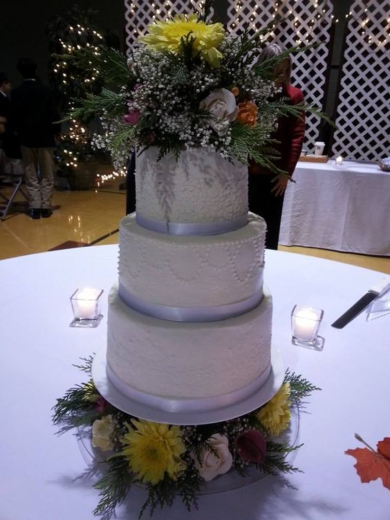 White on white Fall themed wedding cake. Yellow, orange, white, cream, red, burgundy, and baby breath accent the cake.