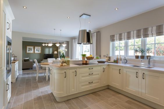 Feature wall to a family room in deep forest Green teamed with an ivory shaker kitchen for a country inspired look and feel. Statement pendant lights create a great talking point. #kitchen