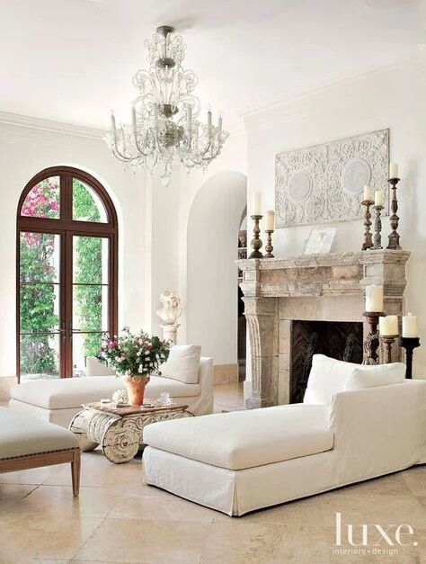 Classic white living room with arched French doors and antique fireplace. Beautiful Classically Refined Rooms