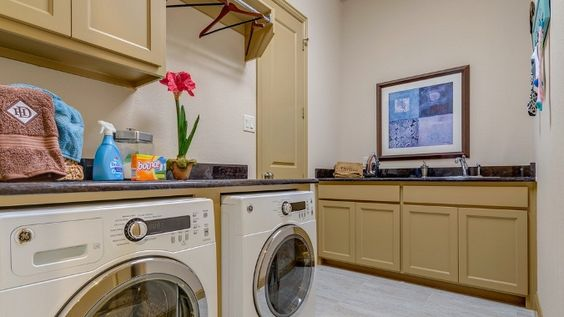 Folding laundry is easy in this utility room by Darling Homes at Mustang Park. Placing a bar above the washer provides the perfect place to hang delicates to dry! #laundryroomtips #laundryroomideas #new #home #laundryroom #Carrollton