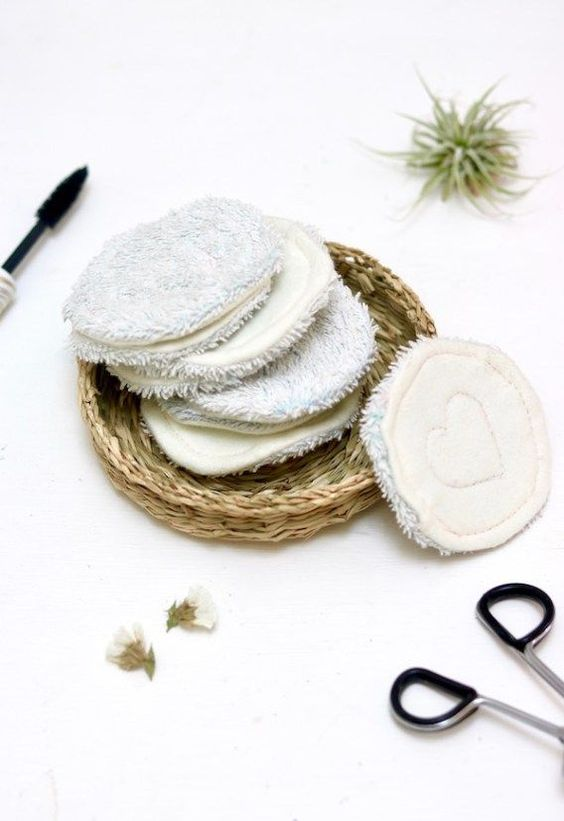 Reuseable makeup remover pads with eyelash curler, air plant, and mascara wand.