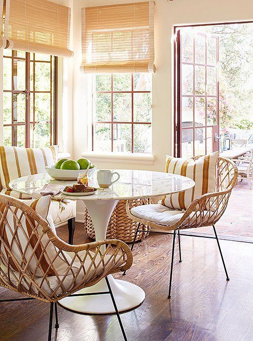 Reese Witherspoon Home Again House in the Movies: Decor Inspiration. Breakfast nook dining room decor with Saarinen table and rattan Midcentury modern dining chairs. Natural rollup shades, wood floor, and happy chic in this California Spanish hacienda house featured in HOME AGAIN starring Reese Witherspoon. #diningroom #breakfastnook #homeagain #saarinen #California #interiordesign