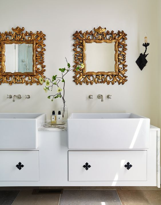 Classic white bathroom with large vessel sinks, wall mount faucets, and gilded framed mirrors. Design by Amy Meier. https://shareasale.com/r.cfm?b=683591&u=1324239&m=11035&urllink=https%3A%2F%2Fwww%2Ewayfair%2Ecom%2Ffurniture%2Fpdp%2Fone%2Dallium%2Dway%2Droxane%2Dchaise%2Dlounge%2Daai3027%2Ehtml&afftrack=
