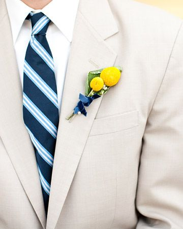 A boutonniere of craspedia and daisies tied with a blue ribbon