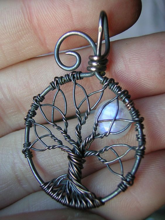 """This pendant was inspired by Celtic folklore and designs. It features the common """"Triquetra"""" or """"Trinity Knot"""" within the branches of the tree. Measuring approximately 1 1/2 inches tall (including the bail) and 1 inch across at the widest area, it was created with a beautiful Rainbow Moonstone moon and oxidized copper wire."""