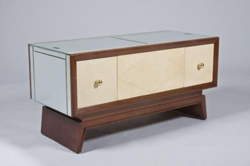 French Art Deco coffee table/cabinet in mahogany with original parchment sides incised with gilt. Mirror top and ends slide apart to reveal parchment lined compartment. Bronze mounts.